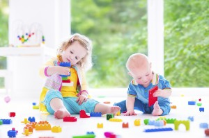 Brother and sister playing with colorful blocks